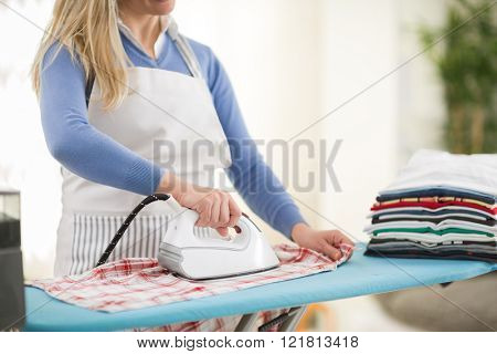 Woman with iron in hand in ironing action