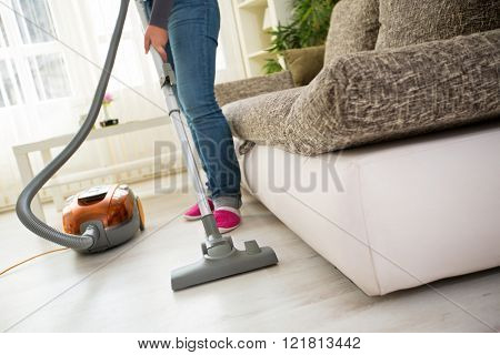 Vacuuming floor in living room with vacuum cleaner
