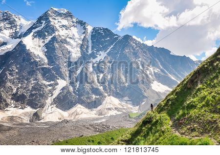 Tourist Walking On A Steep Slope On A Background Of Mountain