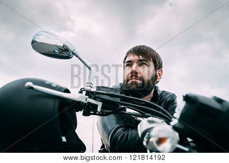 Biker with a beard on his motorcycle in the leather jacket
