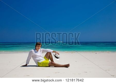 Summer beach. Relax. Successful handsome man resting on exotic beach with blue water and white sand. Vacation Travel. Bliss freedom seashore concept.