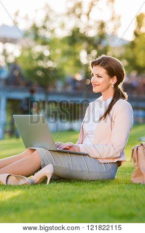 Businesswoman sitting in park working on laptop, sunny summer da
