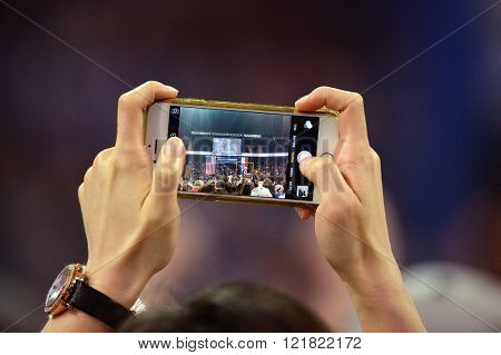 Saint Charles, MO, USA - March 14, 2016: Supporter holds phone during Bernie Sanders campaign rally at the Family Arena in Saint Charles, Missouri.