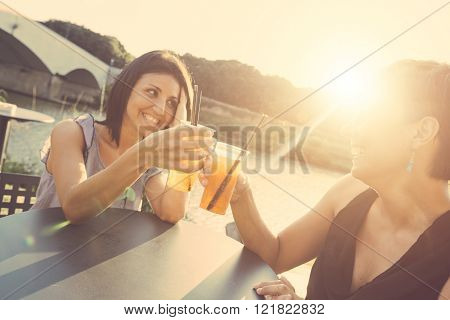 Two Beautiful Women Having A Cocktail Outdoor At Sunset