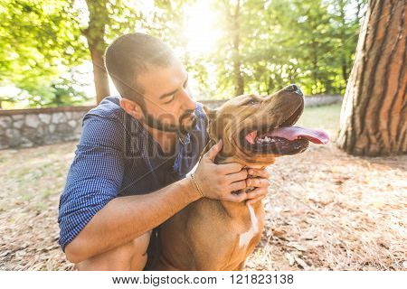 Portrait of a man with dog at park. He is looking at his dog standing with open mouth. The main subject is the dog the man is standing behind it.