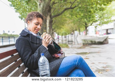 Young Woman Seated On A Bench Having Lunch In London