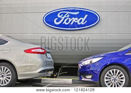 MOSCOW RUSSIA - OCTOBER 10 2015: Logotype of Ford corporation and new Ford Mondeo cars on October 10 2015. Ford is an American multinational automaker.