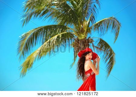 Beauty Carefree Young Girl With Red Hat Relaxing On Tropical Beach With Exotic Palm Tree. Summer Out