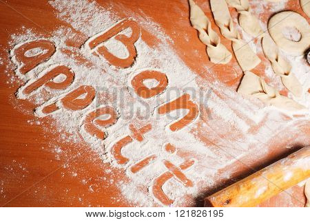 The inscription bon appetit on the table with flour dough and donuts
