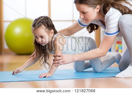Woman with child exercising in sport hall