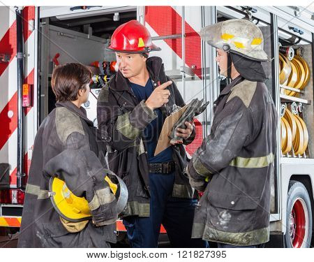 Firefighter Discussing With Colleagues At Fire Station