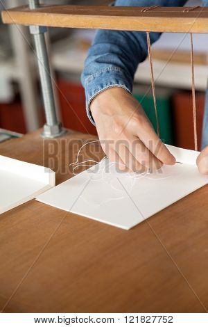 Worker's Hand Inserting Needle In Paper
