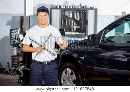 Mechanic Gesturing Thumbs Up While Holding Rim Wrench