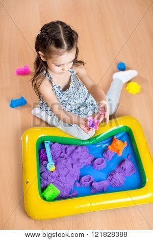 Child girl moulds from kinetic sand in play room.  Preschool.