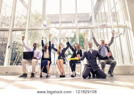 Business team exulting - Happy cheerful businessmen rising arms and throwing documents concepts about success and teamwork