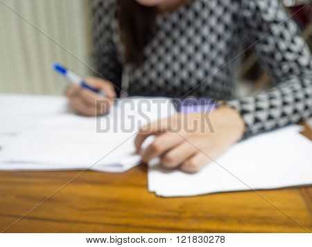 De-focused And Blur Image Woman Writing Something On Background