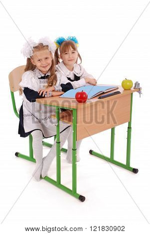Little Schoolgirls Sitting At A Desk