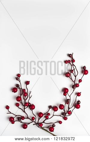 Red berries holly on white. Red Christmas ornaments frame. Image of Christmas. Top view with copy space.