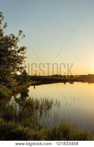 Riverside at sunset next to fields dramatic landscape