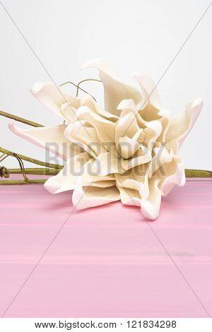 Elegant spring flower fake gardenia on rustic wooden table. For wedding background image.