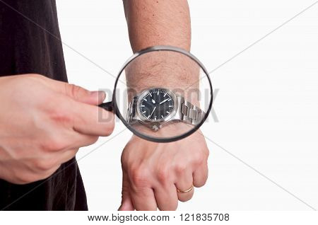 man with magnifier in hand looking at his watch on white background