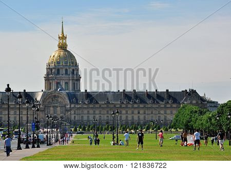 PARIS FRANCE - MAY 7: Men playing football on the grass field near the Invalides building in Paris on May 7 2011. Paris is the most famous and touristic city in Europe.