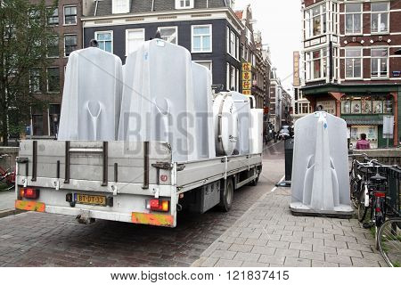 AMSTERDAM, HOLLAND - SEPTEMBER 9, 2011: Truck with public urinals and one placed into position on bridge