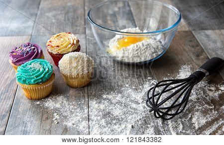 Fresh baked cupcakes with kitchen utensils on wodden surface
