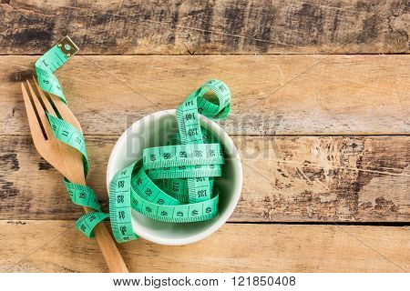 Green measuring tape in ceramic cup on wooden table background