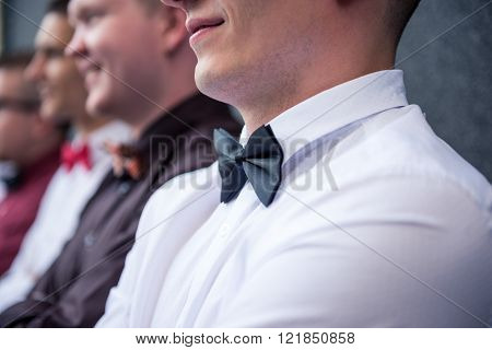 Elegant men with bow tie standing against the wall. Bow tie in focus.