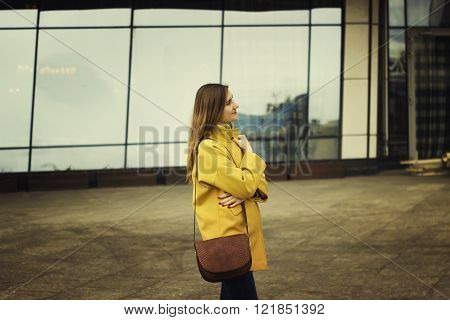 Beautiful young woman stand on the high-rise buildings backround in the spring time