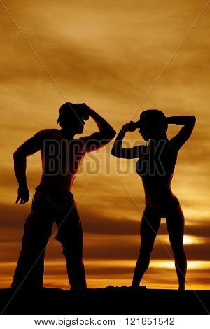 A silhouette of a cowboy leaning in to his woman.