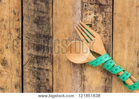 Green measuring tape and wooden spoon and wooden fork on wooden table background