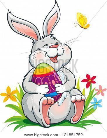 Lovely  bunny sitting on grass and holding painted easter egg