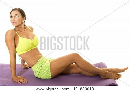 A woman sitting in her fitness clothes looking over her shoulder.