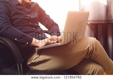 Freelance work. Casual dressed man sitting in chair inside his flat working on computer pointing with finger