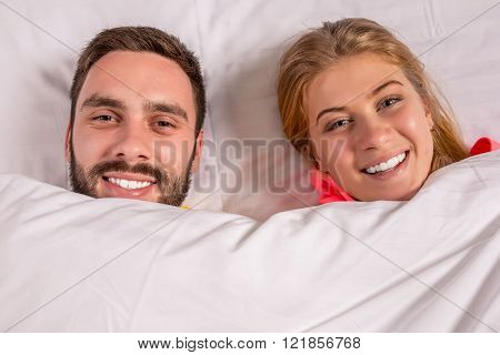 Young lovely couple lying in a bed, looking at camera