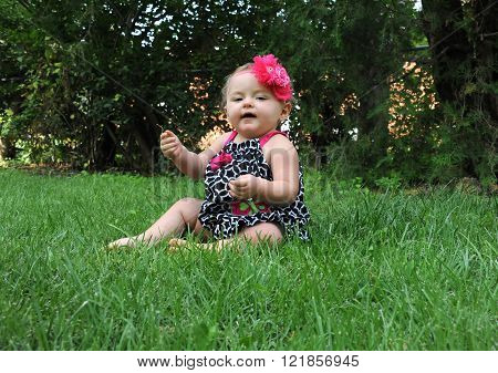 Baby girl sits outside and plays with blades of grass. Her expression is half pleased and half amazed at the grass in her hand.
