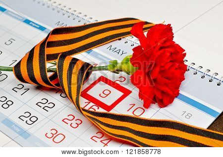 Victory Day card - bright red carnation wrapped with George ribbon lying on the calendar with framed 9th May date