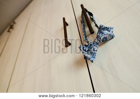 Bow tie hanging from a closet in natural light