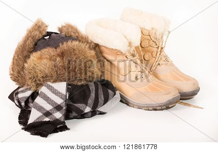 Winter boots and cap. Warm clothes for a cold season. A close up on a light background