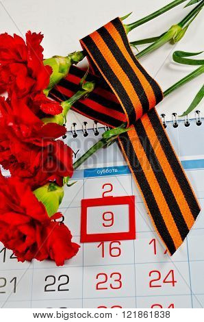 Victory Day card - three red carnations wrapped with George ribbon on the calendar with 9th May date- holiday that commemorates the victory of Soviet Union in the Great Patriotic War.