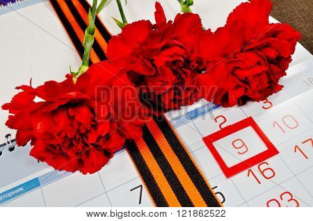 Postcard for Victory Day in Great Patriotic War in Russia- St George ribbon and red carnations over the calendar with framed 9th May date