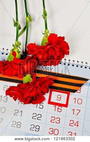 St George ribbon and red carnations above the calendar with 9th May date - the day of victory in Great Patriotic War in Russia