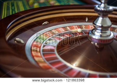 Casino roulette wheel with red sector twenty-one and ball.