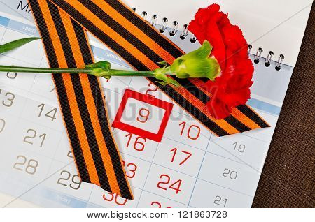 Victory Day greeting card - bright red carnation with George ribbon lying on the calendar with 9th May date