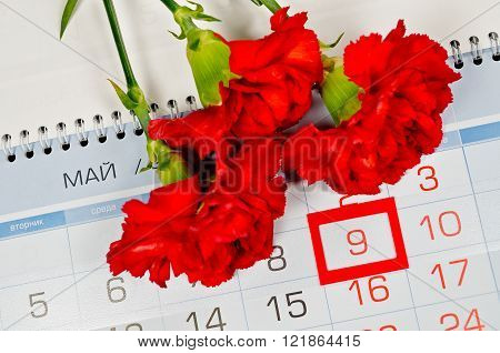 Bouquet of bright red carnations above the calendar with framed 9th May date - the day of USSR victory in Great Patriotic War in Russia