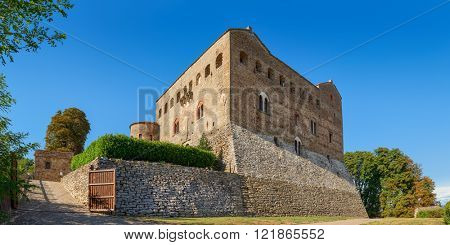 Old medieval castle of Prunetto under blue sky in Piedmont, Northern Italy (panorama).