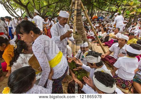 SANUR, BALI - MAR 18, 2016: Unidentified local people during performed Melasti Ritual. Melasti is a Hindu Balinese purification ceremony and ritual is held several days prior to the Nyepi holy day.