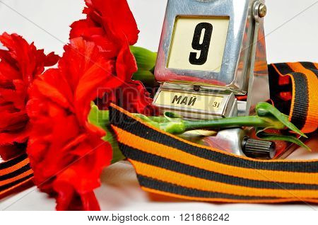 Closeup of vintage metal desk calendar with 9th May date and George ribbon and red carnations - Victory Day concept